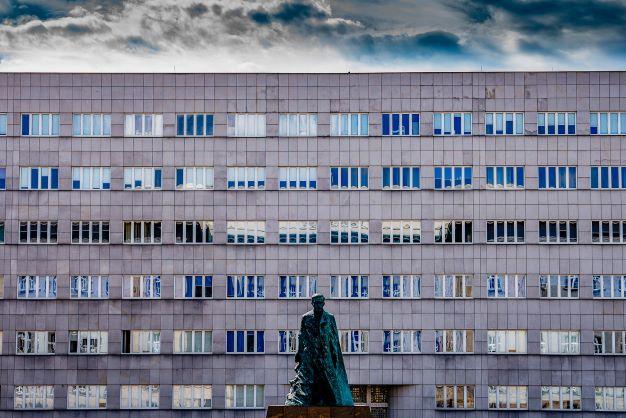 Fotografia przedstawia gmach budynku wydziału humanistycznego UŚ. Na pierwszym planie pomnik Wojciecha Korfantego. Autor: Moderna © Krzysztof Szlapa 2021